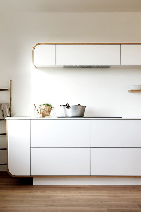 a catchy retro yet contemporary kitchen with a smartly incorporated hood and curved cabinets is a stylish space