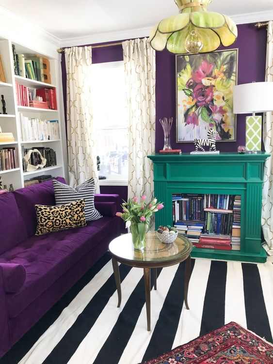 a colorful living room with a depe purple accent wall and a matching sofa, a striped rug, a floral pendant lamp and an emerald fireplace with books
