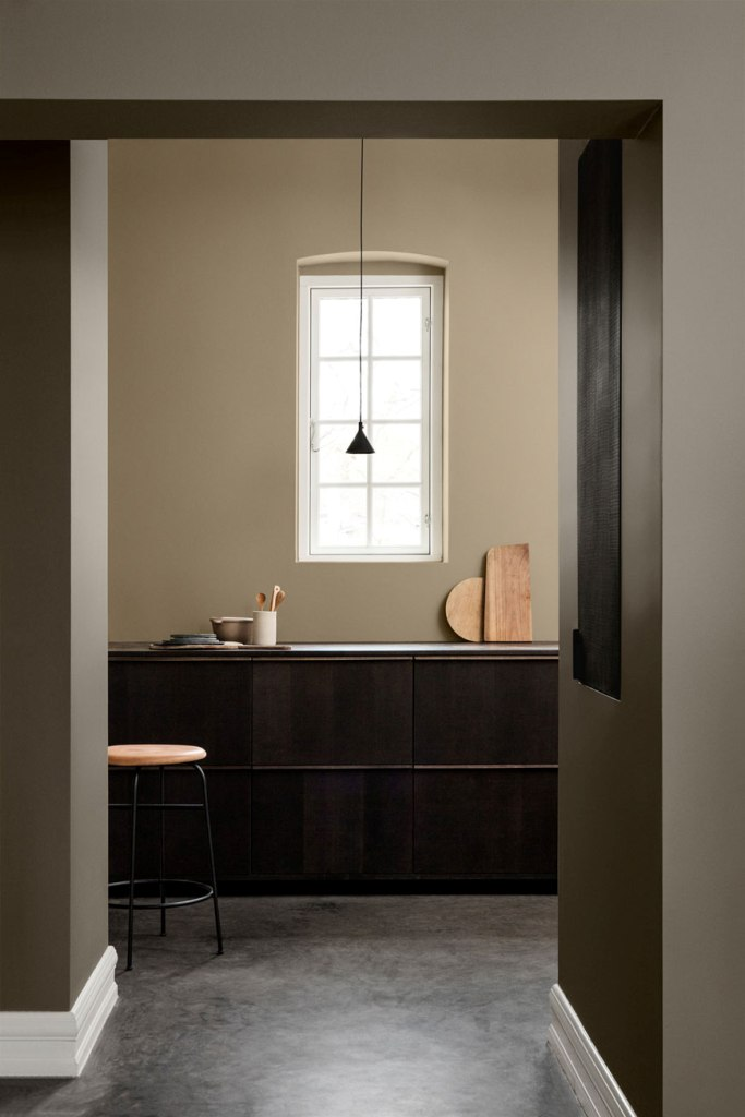 a minimalist kitchen done with olive green walls, sleek dark cabinetry, a black pendant lamp and light stained wood