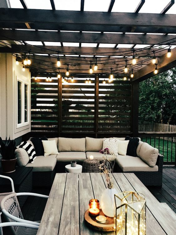 a modern backyard with stylish furniture, string lights over the space and some candles and lights right on the table