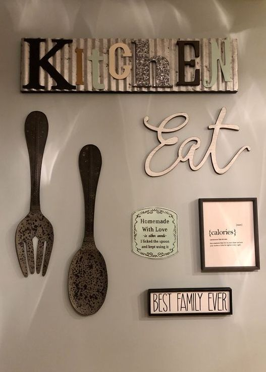 05 kitchen wall decor with a metal sign, an EAT sign, some large cutlery pieces and vintage mini signs on the wall