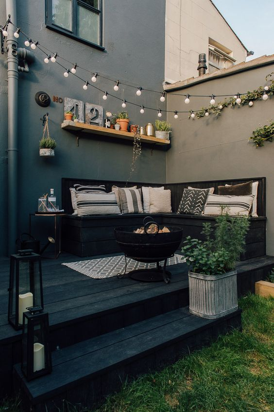 a Nordic backyard space with graphic pillows, lots of potted plants and string lights over the space