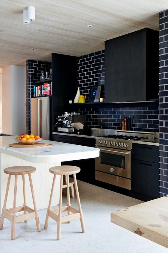 a chic modern black kitchen with a matching hood, a navy subway tile backsplash, metal countertops is stylish and bold