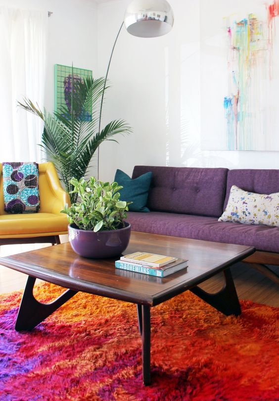 a colorful living room with a purple sofa, a yellow chair, a chic stained coffee table and bright artworks and a floor lamp