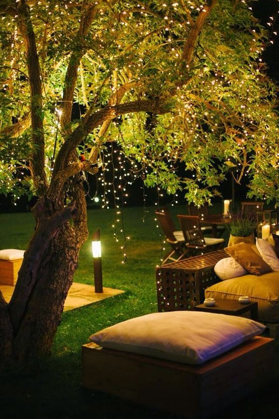 a contemporary backyard space with comfy furniture and hanging string lights over the space and outdoor lamps