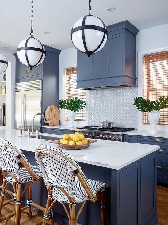 a cool tropical kitchen with blue cabinets and a matching hod, a tile backsplash, white stone countertops and catchy stools