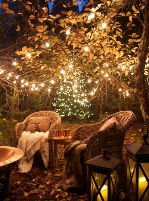 a cozy backyard with rattan chairs, lots of lights on the trees and candle lanterns and a fire pit is very inviting