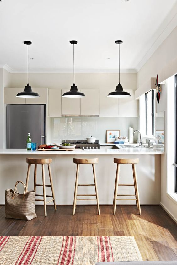 a lovely ivory kitchen wiht sleek cabinets, white stone countertops and an integrated hood plus black pendant lamps