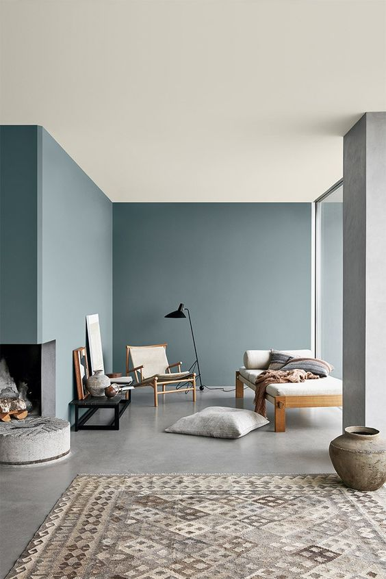a minimalist living room with pale blue walls and a built-in fireplace, chic furniture and touches of black for drama