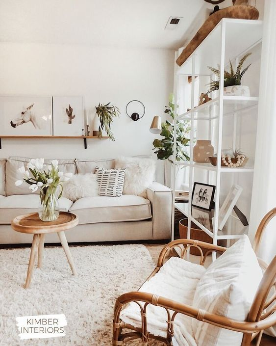 a neutral and cozy living room with a rattan chair, a neutral sofa, a large storage unit and lots of potted greenery