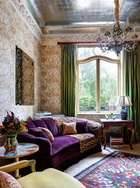 a sophisticated vintage living room with printed wallpaper, a purple sofa, a lovely chandelier, green curtais and a printed rug