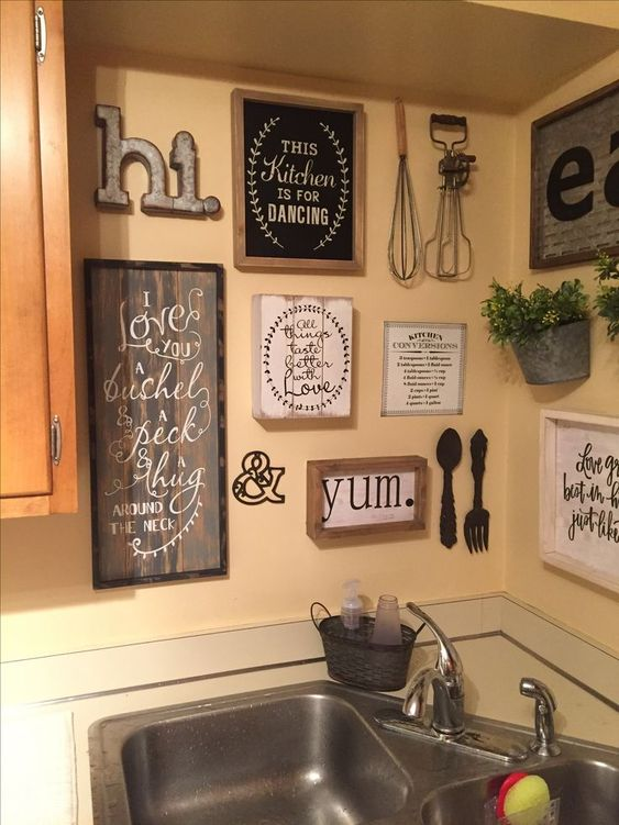 vintage and rustic kitchen wall decor with signs in frames, potted greenery, metal monograms and letters and kitchen stuff