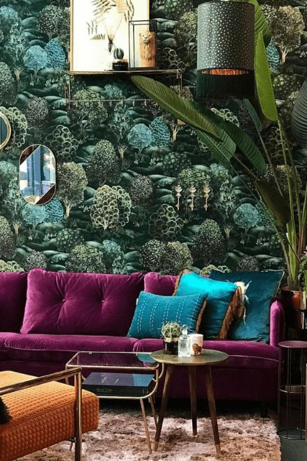 a maximalist living room with a botanical accent wall, a purple sofa, green pillows, a pendant lamp and a potted plant plus mismatching tables