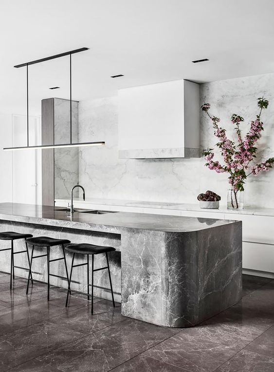 a minimalist kitchen with sleek white cabinets and a matching hood, a grey stone curved kitchen island and sleek lights