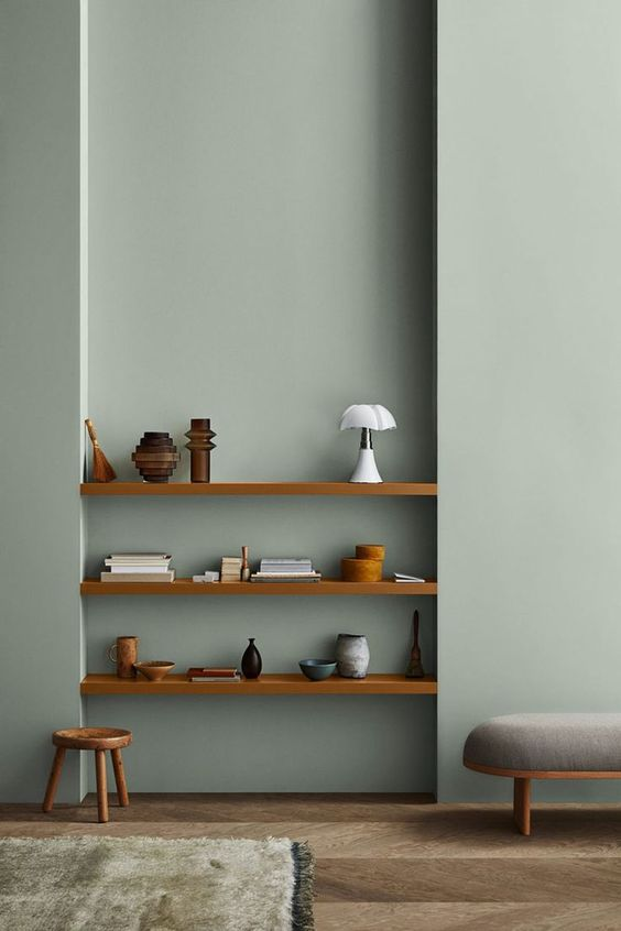 a minimalist space with slate blue walls, built-in shelves and stained and grey furniture is chic and cool