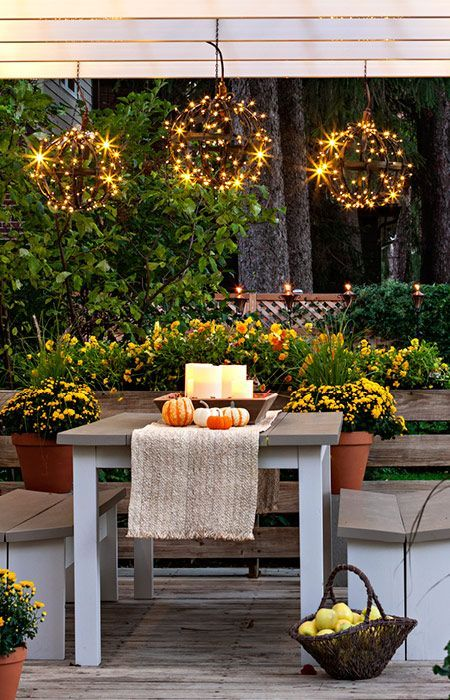 a bright fall deck with stylish and simple furniture, potted blooms, candles in a bowl for a centerpiece and light spheres over the table