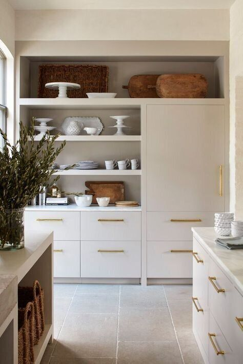 a lovely neutral kitchen with cool cabinets, gold handles, stone countertops and closed and opened storage units