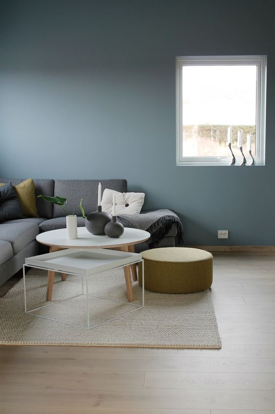 a minimalist Scandinavian space with blue walls, a grey sectional, mismatching tables and a round mustard ottoman
