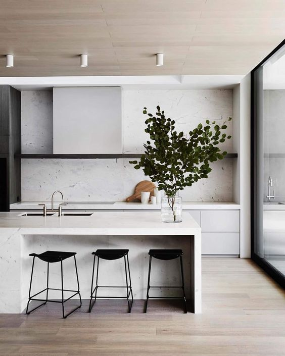 a minimalist off-white kitchen with sleek cabinets, a hood that matches them and black stools and a white stone backsplash