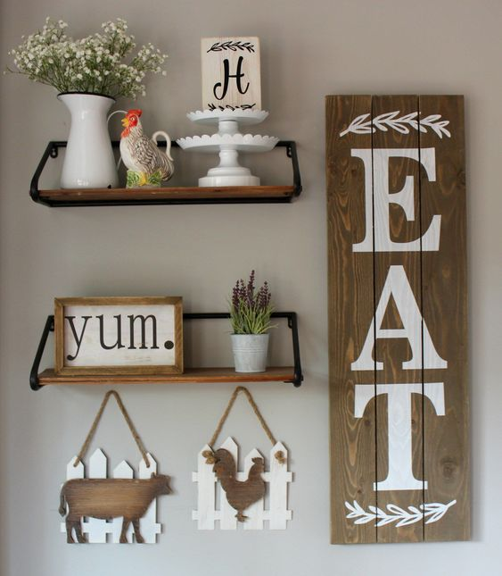 kitchen wall decor wiht a rustic sign, a frame one, plaques with animal silhouettes and potted plants and blooms
