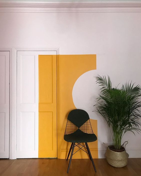a chic minimalist space with a bold yellow touch on the wall and door is a bright accent to cheer up the space