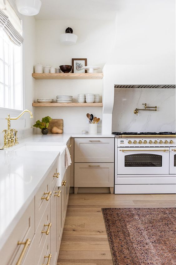 a chic neutral kitchen with gold fixtures and handles, built in shelves and cookers is a beautiful space
