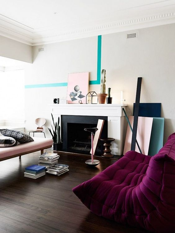 a contemporary living room with a non-working fireplace, a blush couch and a deep purple sofa, color blocking and books