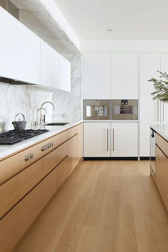 a minimalist two-tone kitchen with an incorporated hood and white marble countertops and a backsplash is welcoming