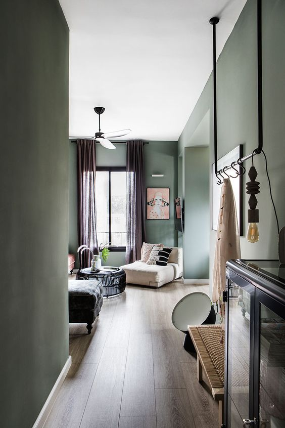 a beautiful Scanndinavian home with light green walls, various chic furniture, mauve curtains, black dramatic touches