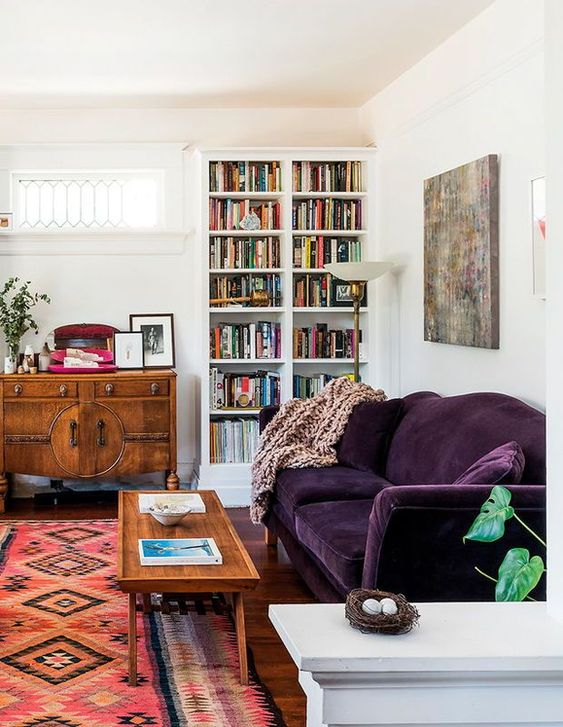 a mid-century modern living room done in neutrals and filled with color - a printed rug, a deep purple sofa, stained furniture and a built-in bookcase