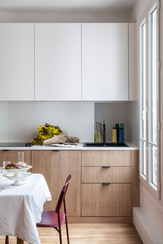 a minimalist two-tone kitchen with sleek cabinets, an incorporated hood and white countertops and a backsplash is chic