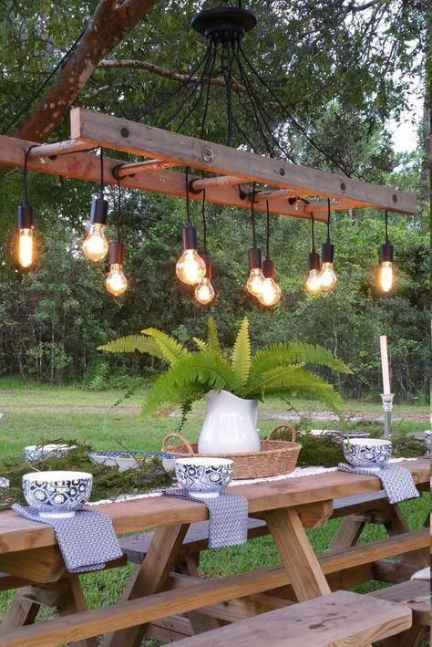 a quirky outdoor dining space with simple wooden furniture and a catchy ladder chandelier with bulbs is wow