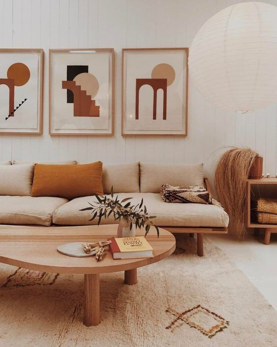 a welcoming boho living room with a cool sofa, a low table, blonde wood items, a printed rug and a lovely gallery wall