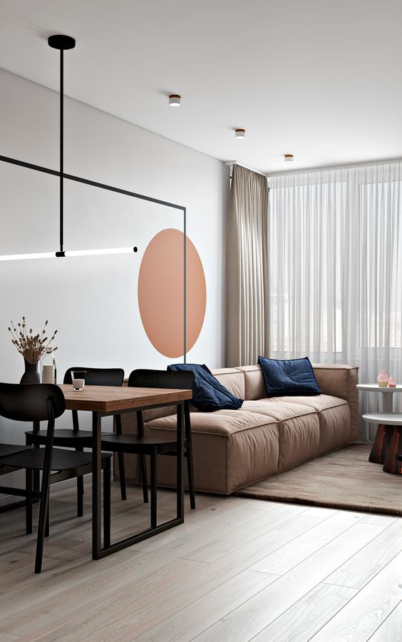 a bold terracotta circle on the wall is a single accent in this space that gives it life and eye-catchiness