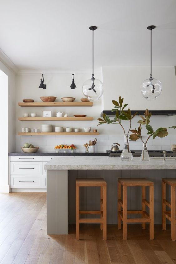 a modern farmhouse kitchen with white shaker cabinets and a matching white hood that is seamless in front of the wall, a grey kitchen island