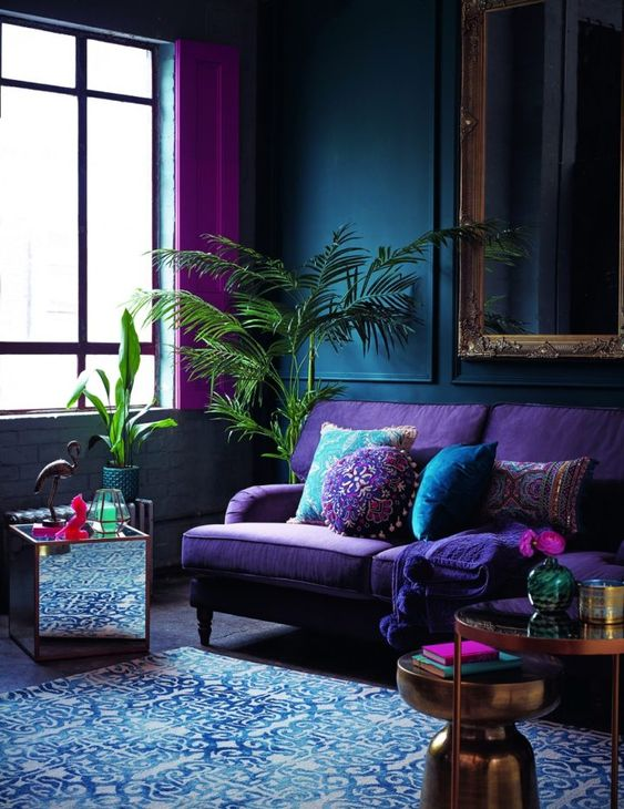 a moody living room with navy paneled walls, a purple sofa, metallic tables and a mirror one, a blue rug and hot pink curtains