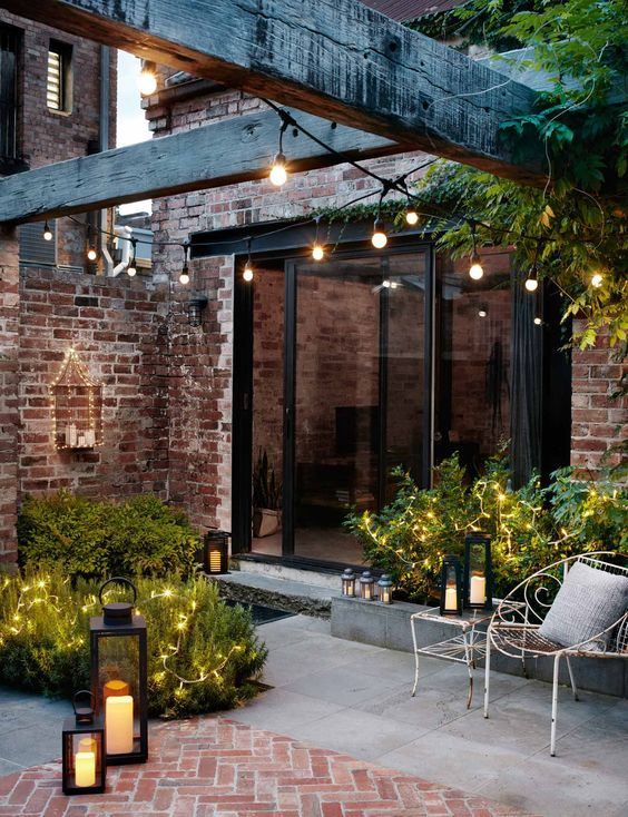 a refined backyard with fairy lights on plants, string lights over the space and candle lanterns all around