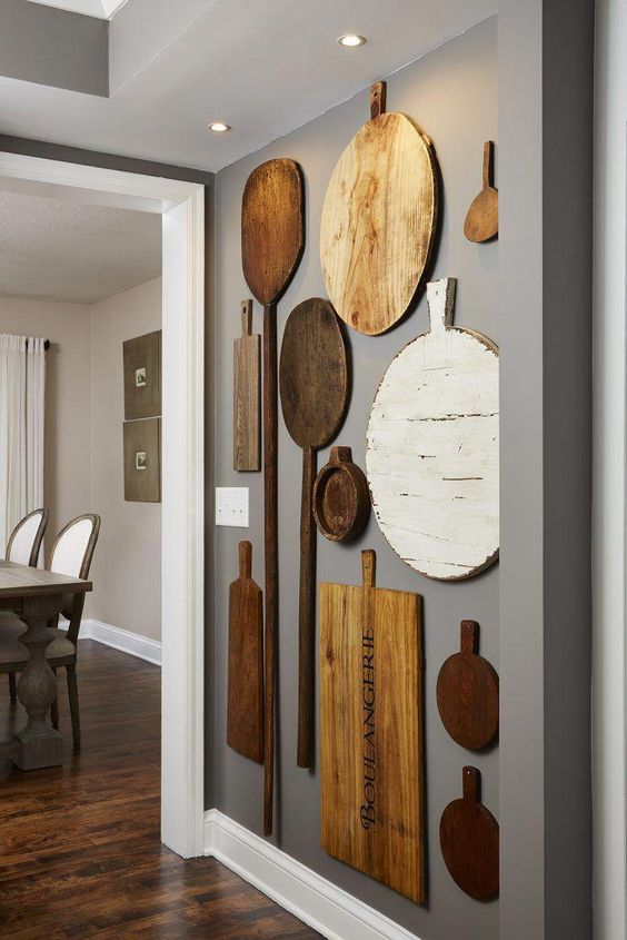 rustic kitchen wall decor with mismatching cutting boards and oars is a lovely idea for a farmhouse space