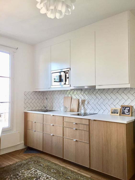 a modern kitchen with sleek white cabinetry and light stained lower ones plus a herringbone backsplash is lovely