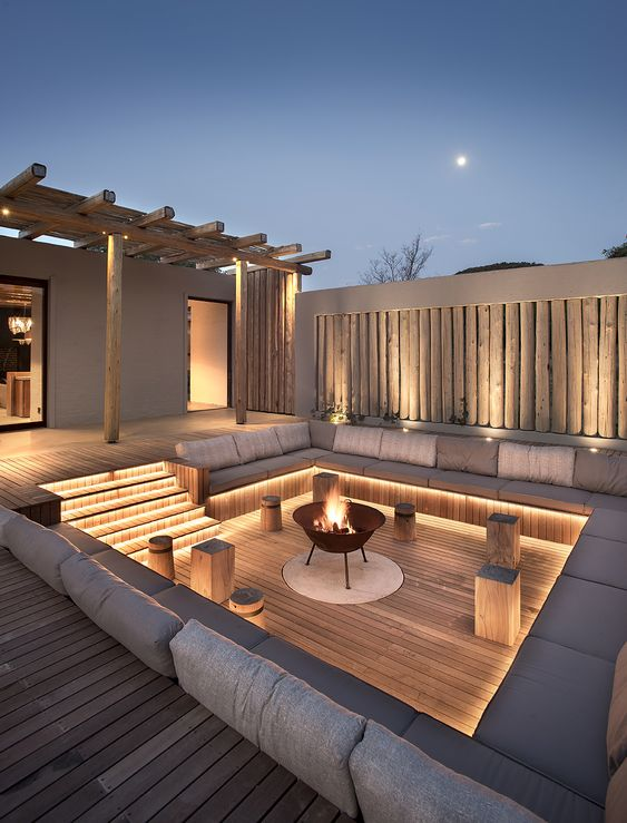 a refined contemporary backyard with built-in lights and a fire pit is a very welcoming and stylish idea