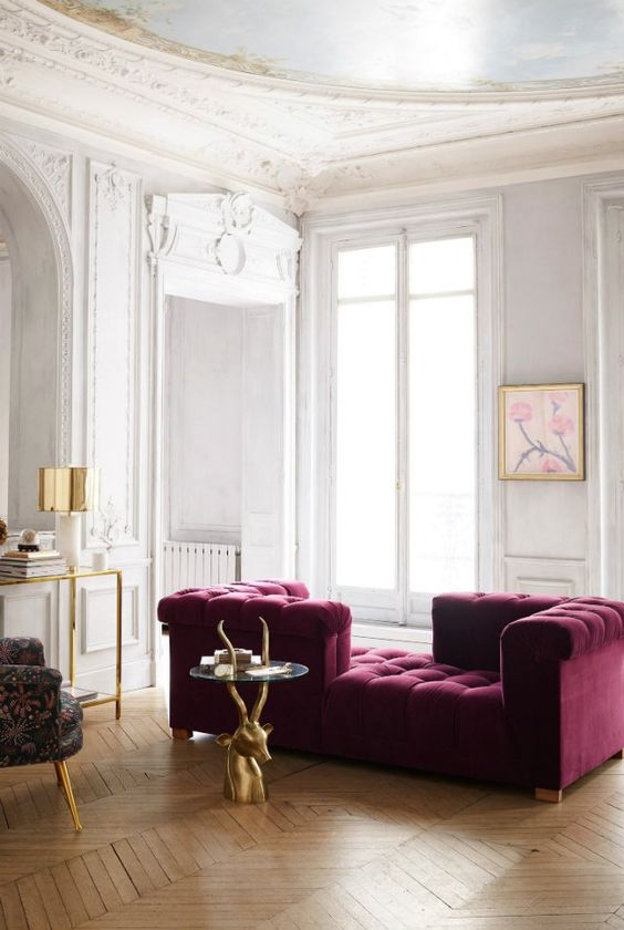 an exquisite neutral living room with a purple couch of velvet, a glass and gold console, a quirky chair and a cool antler table