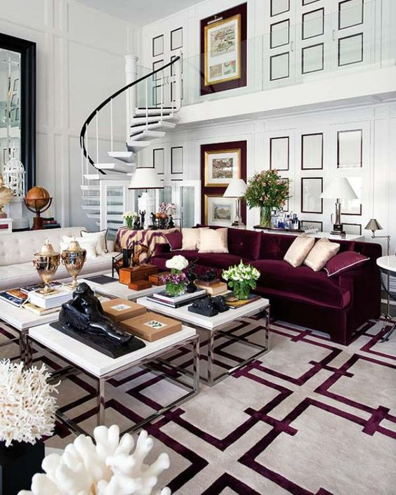 a beautiful living room with white paneled walls, a creamy and a purple sofa, a cluster of coffee tables and a printed white and purple rug