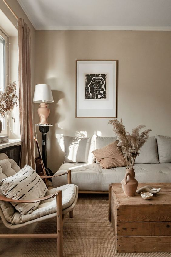 15 a lovely eclectic living room with grey walls, grey seating furniture, a wooden chest as a coffee table, warm touches