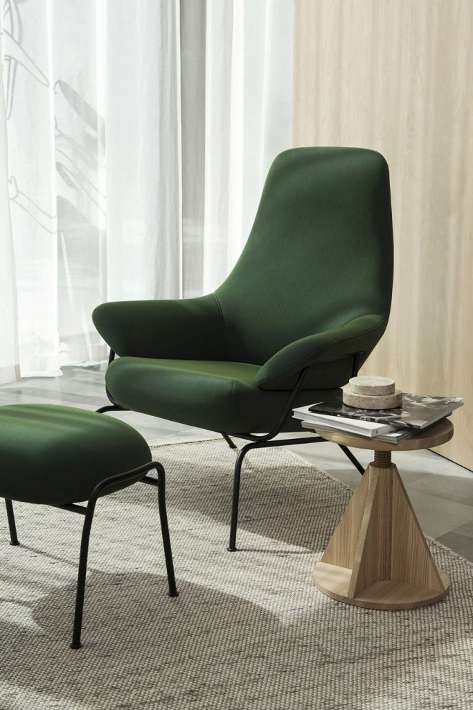 a stylish minimalist space clad with light-stained wood, a bold green chair and a matching footrest and a small round wooden table