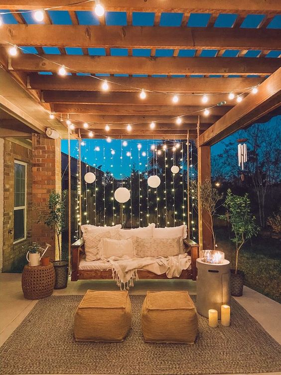 vertical and usual string lights plus paper lamps and candles and a modern fire pit is a stylish idea for a backyard