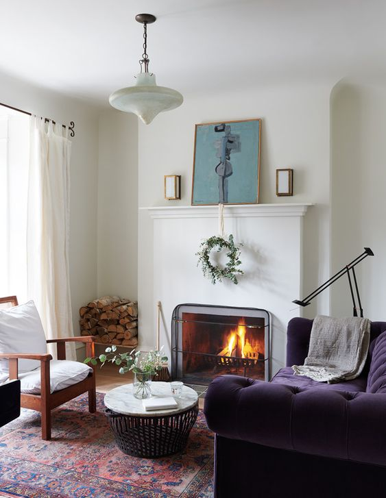 a beautiful neutral living room with a fireplace, a mantel with decor, a white chair and a gorgeous deep purple sofa and a round table