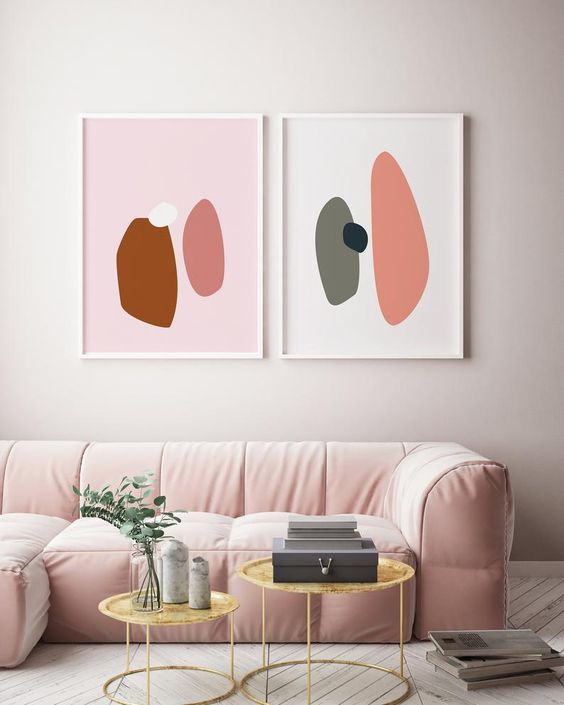 a chic minimalist living room done in neutrals but accented with a light pink sofa, round tables and bold artworks