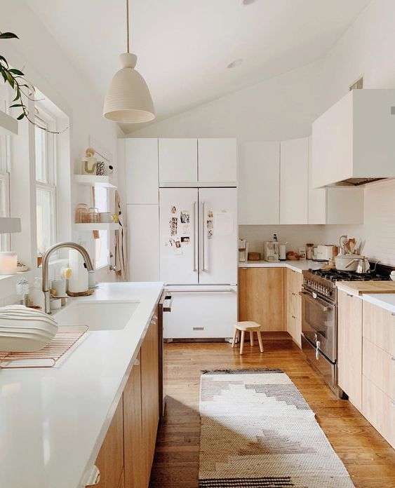 a neutral modern kitchen with light stained cabinets, white countertops and white upper cabinets plus a white hood that loosk seamless here