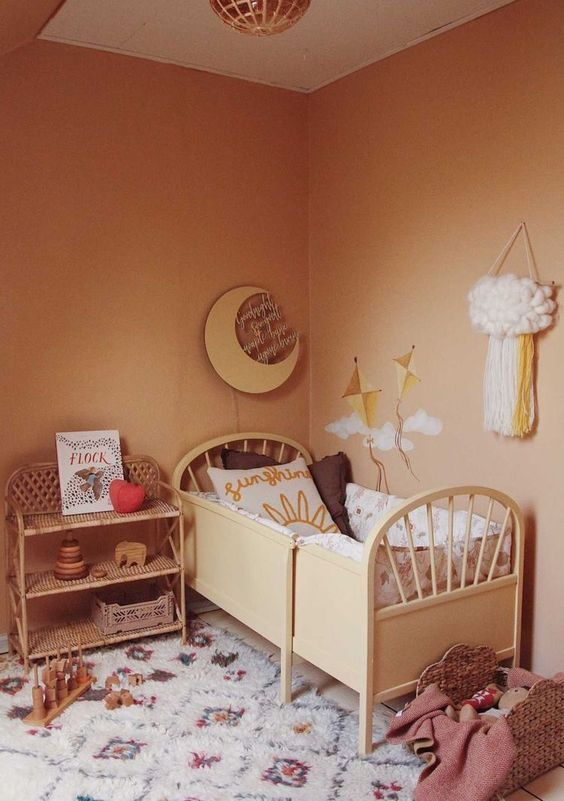 a warm earthy tone kid's room with warm colored walls, stylish furniture, printed textiles and lots of toys