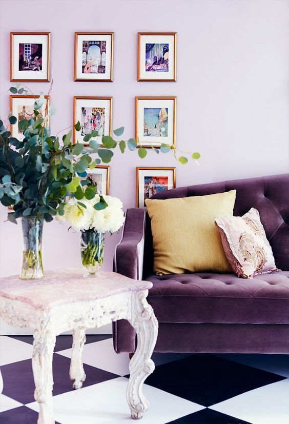 a chic living room with lilac walls, a purple sofa, a refined carved stool and a lovely gallery wall is wow